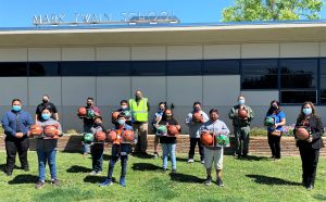 Students hold donated sports equipment alongside prison employees and school staff.