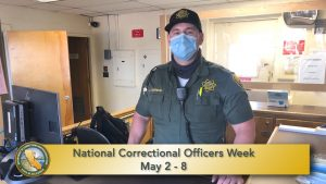 Correctional officer stands in a prison office.