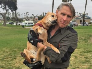 Bruce McGowan holds a dog while standing in a park.