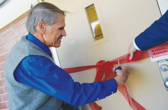 Bruce McGowan cuts the ribbon on a library.