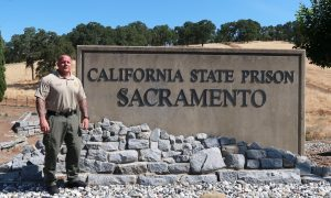 Correctional sergeant stands beside California State Prison Sacramento sign.