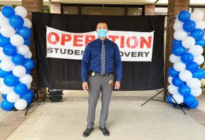 """CIW Lt. Andrew Mendoza stands in front of a school banner that reads """"Operation Student Recovery""""."""