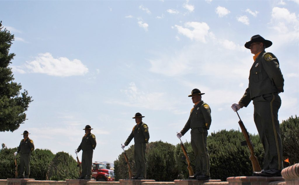 Men in uniform stand in a line to honor CTF's 75 years of service.