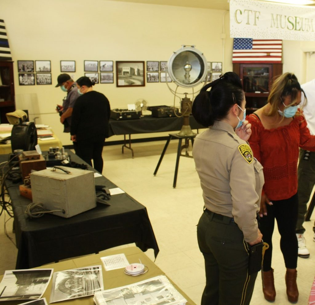 A prison museum with people looking at items.