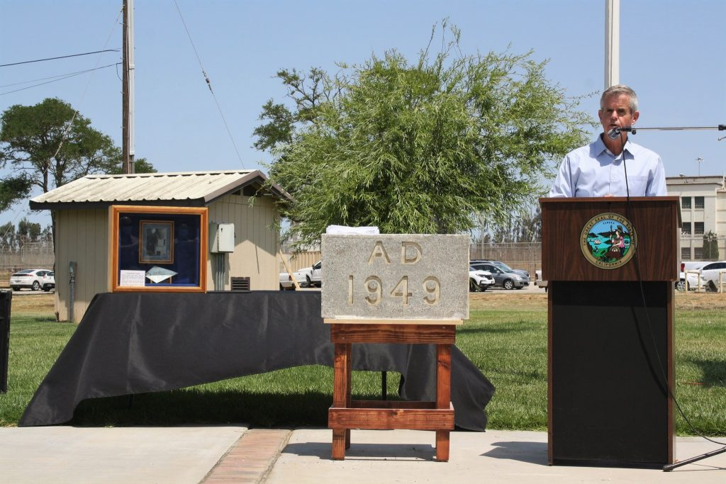 Man at lectern talks about prison's 75 years.