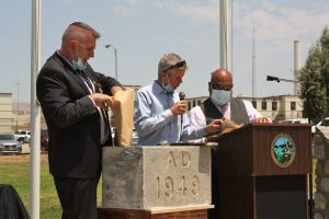 Three people open a time capsule at a ceremony marking 75 years.