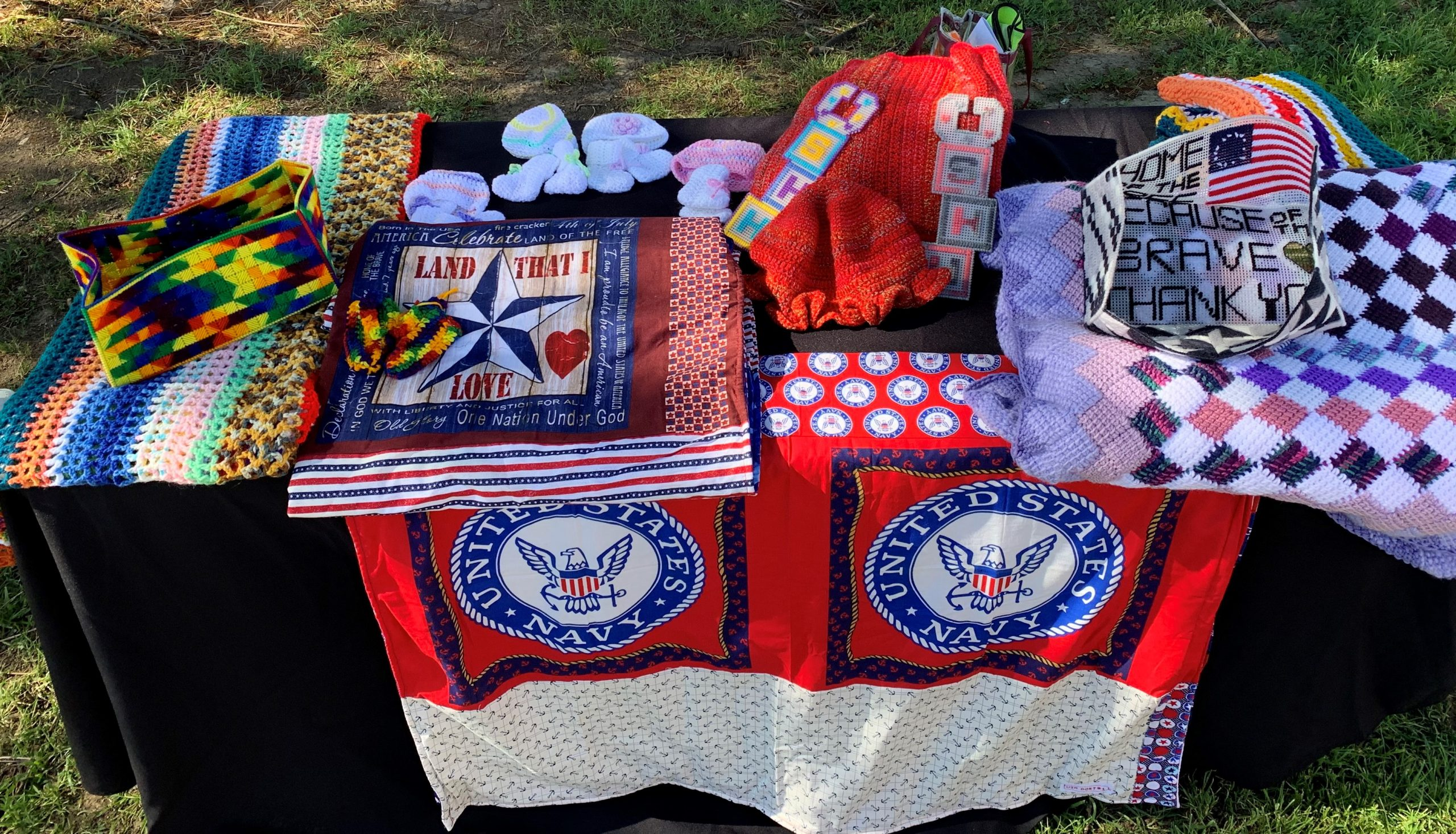 Table filled with hand-crafted clothing and blankets.
