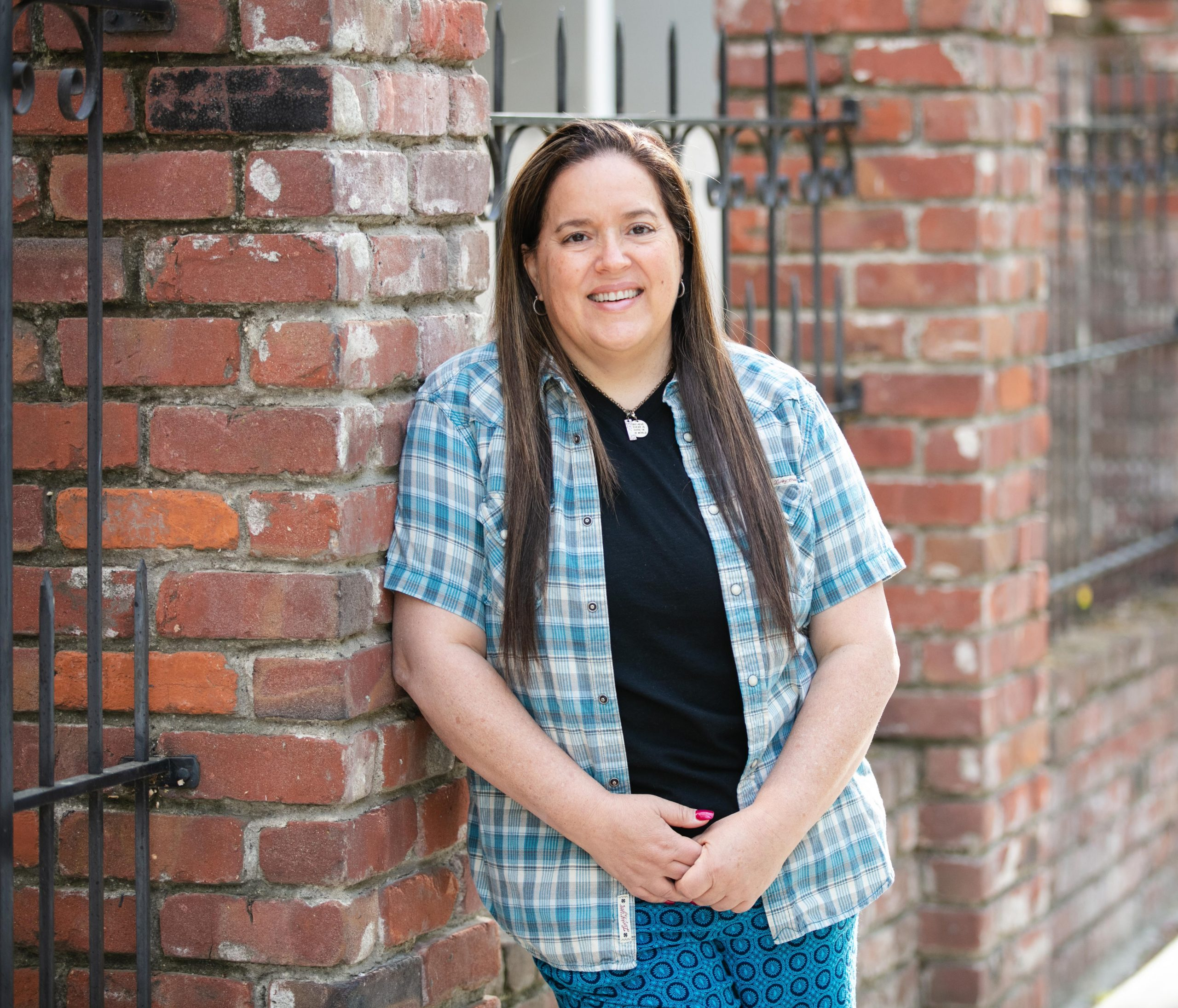 Woman facing camera leaning against brick post.