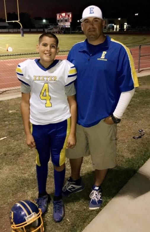 Man standing with young man in football uniform.
