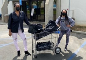 Two women with black bags full of clothing.