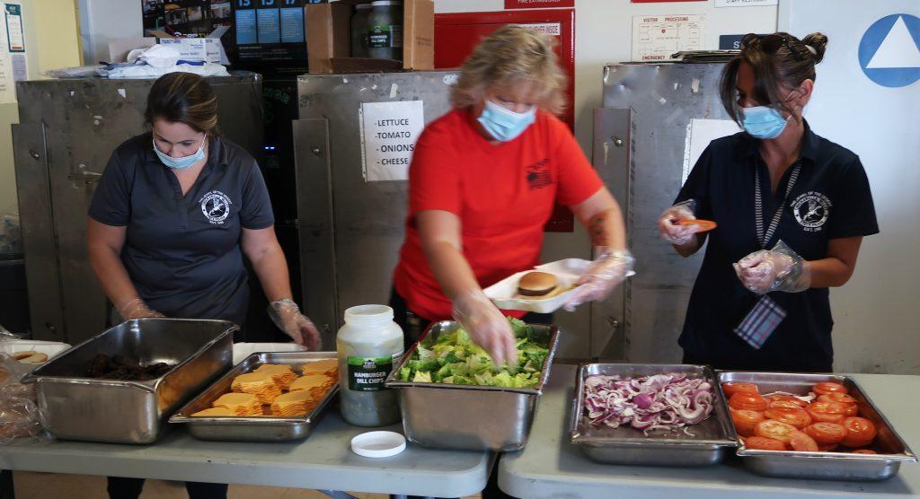 Three people prepare burgers.
