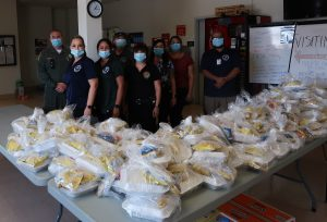CVSP employees stand behind tables of food.