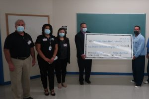 A large donation check is held in a prison.