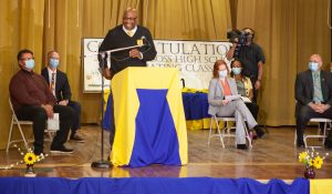 Man speaks from lectern at DJJ graduations while others are gathered on a stage.