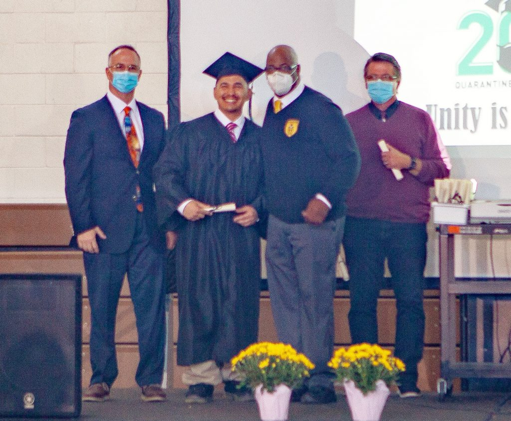 Three people stand beside a young man wearing a cap and gown.