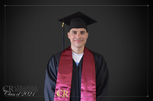 A man wears graduation cap and gown.
