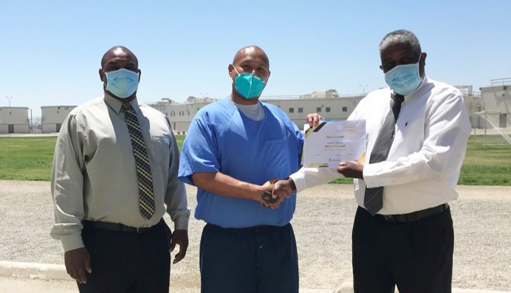 Prison artist poster contest winner and two staff members with a certificate.