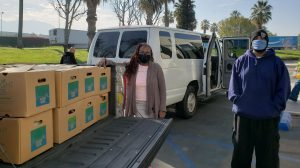 Man and woman stand beside a truck bed full of boxes.