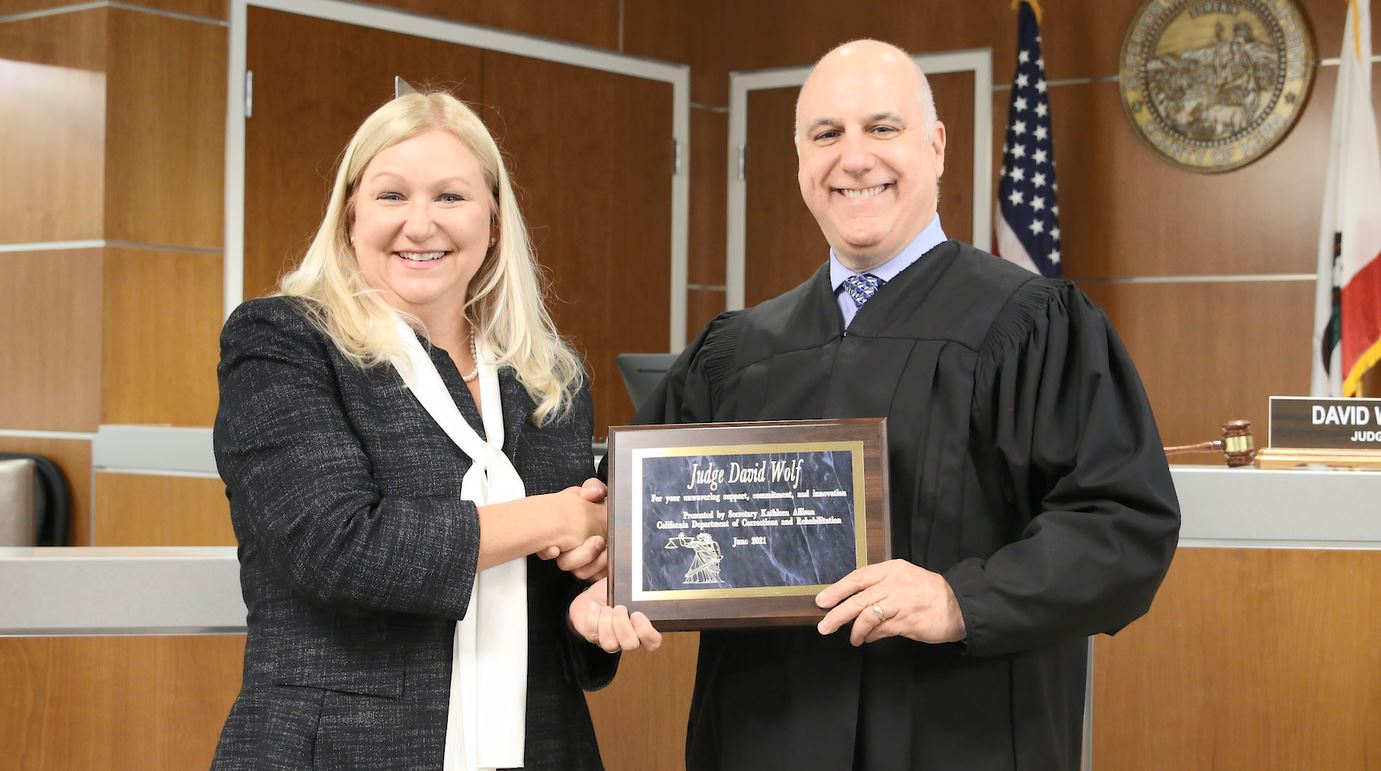 Woman presents plaque to a judge wearing robes.