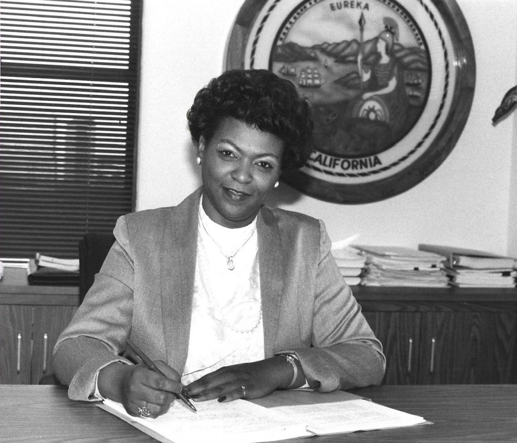 Woman sitting at desk with California seal in the background.