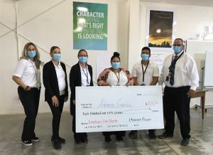 Six people wearing masks hold an over-sized check made out for $250 to Adriana Garcia from the Phoenix House.