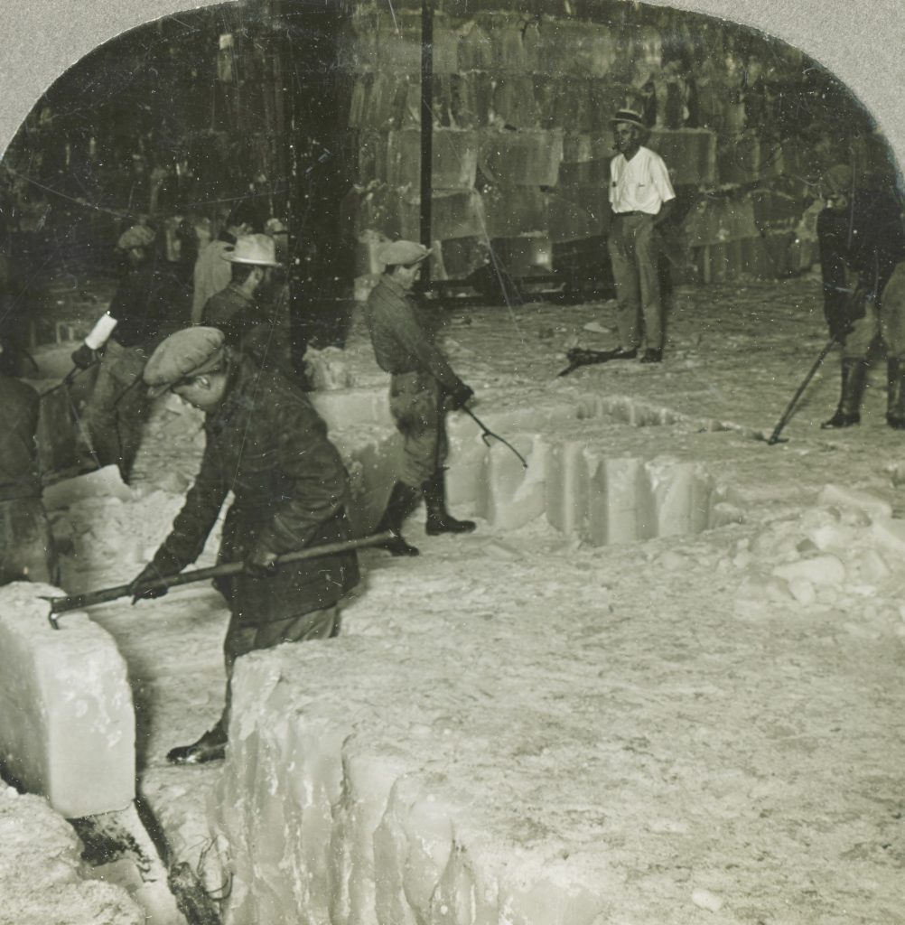 Blocks of ice are moved with hooks and poles into rail cars.