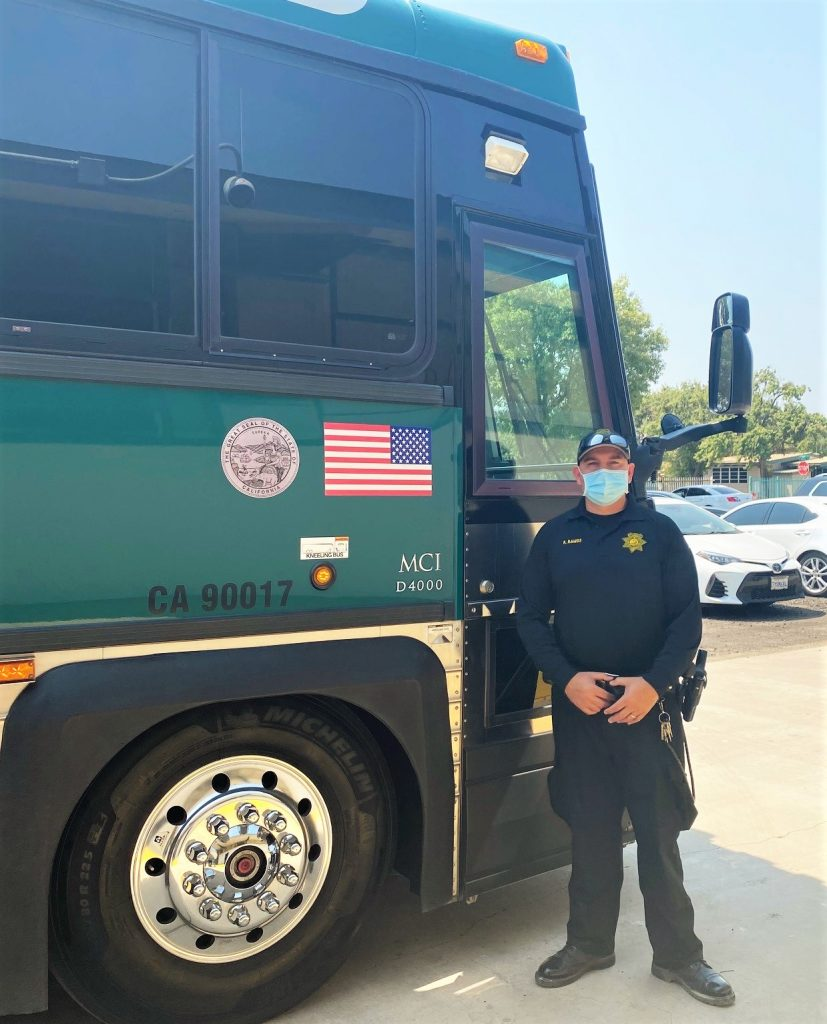 CDCR transportation bus and officer in a parking lot.