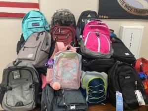 Backpacks with school supplies are piled up in the Transportation Unit office.
