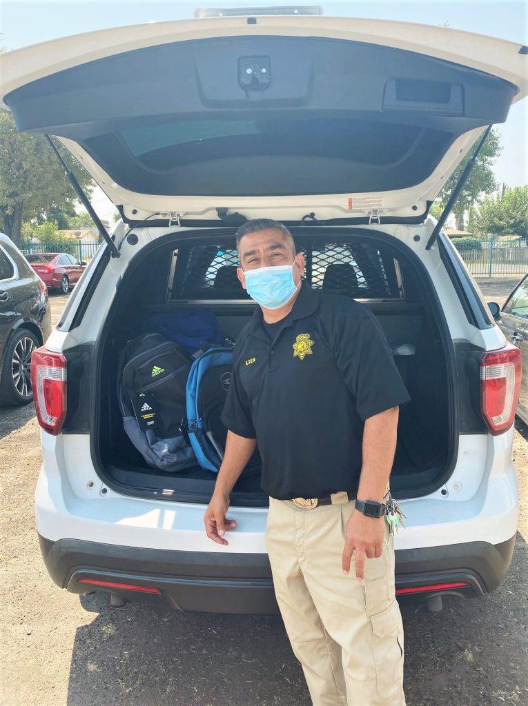 Transportation Unit officer distributes backpacks at a school.