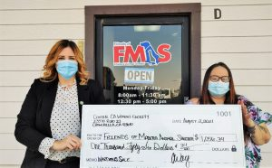 Two people hold oversized check from CCWF to help animals.