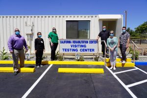 Staff stand at a sign that says California Rehabilitation Center Visitor Testing Center.