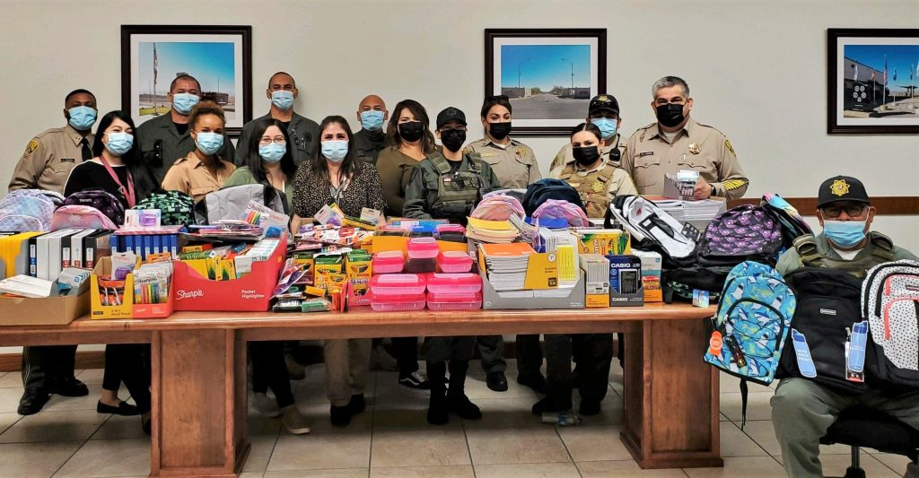 Calipatria prison staff and a table full of school supplies.