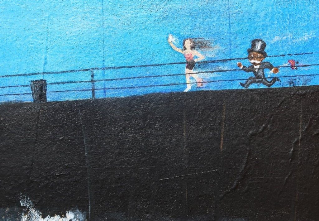The California Men's Colony mural shows a tuxedo wearing chasing a girl on roller skates.