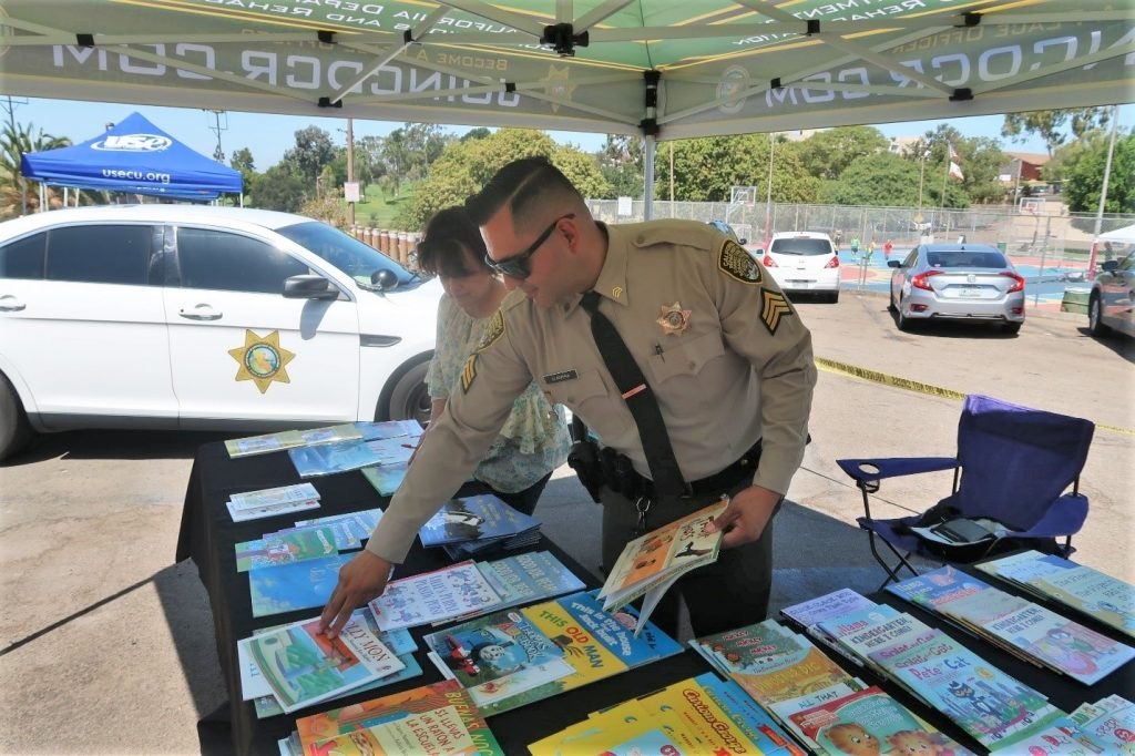 Two correctional staff prepare books for San Diego students.
