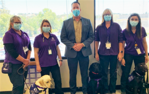 Service dogs with four women wearing purple and the Sacramento prison warden.