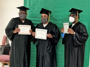 Three graduates in caps and gowns.