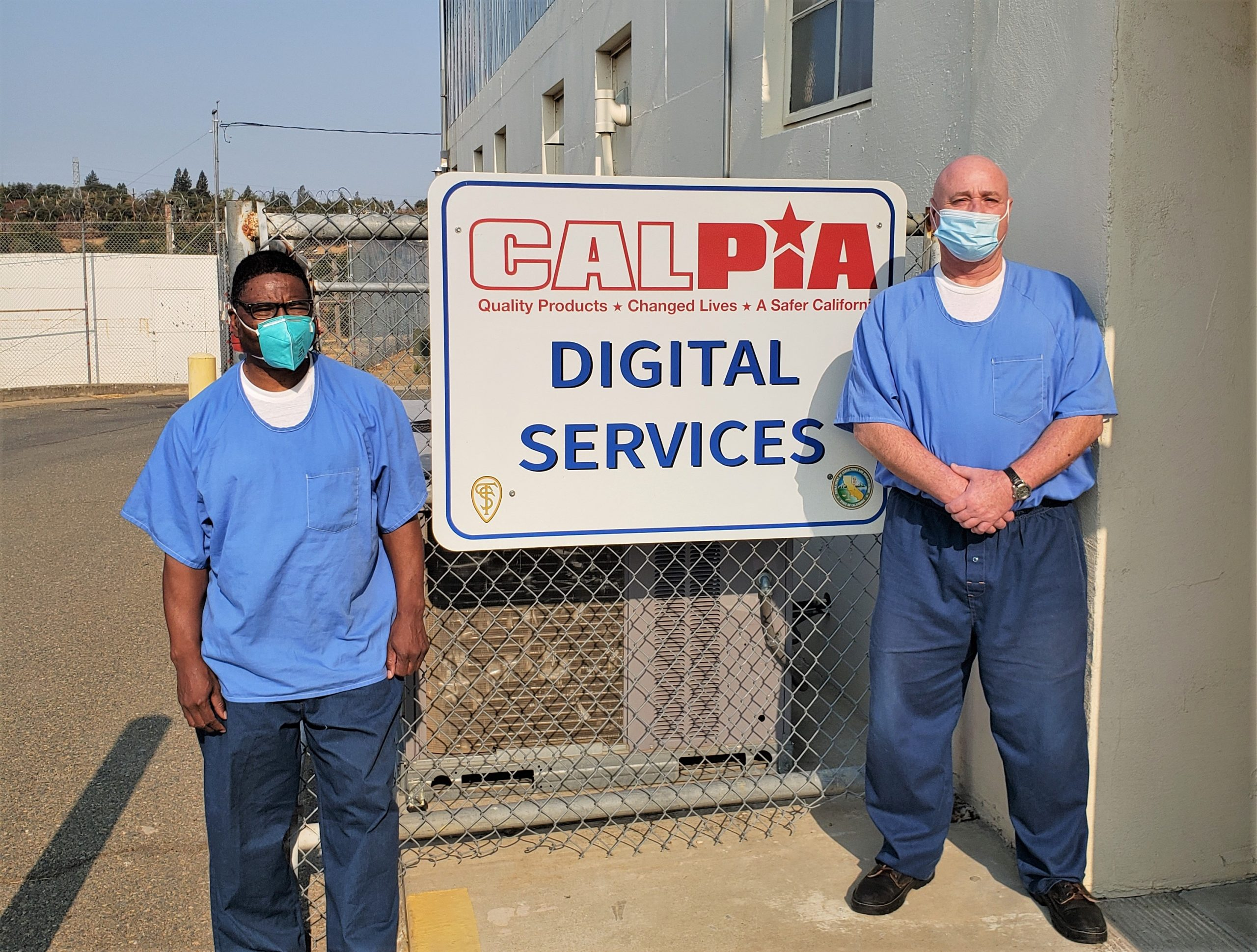 Two incarcerated men stand beside a CALPIA digital services sign.