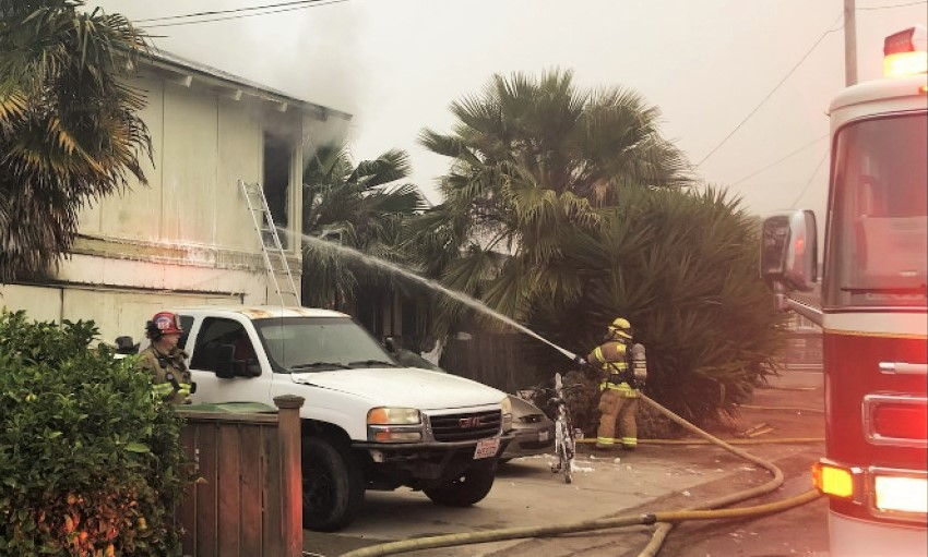 Firefighter sprays water into a house fire.
