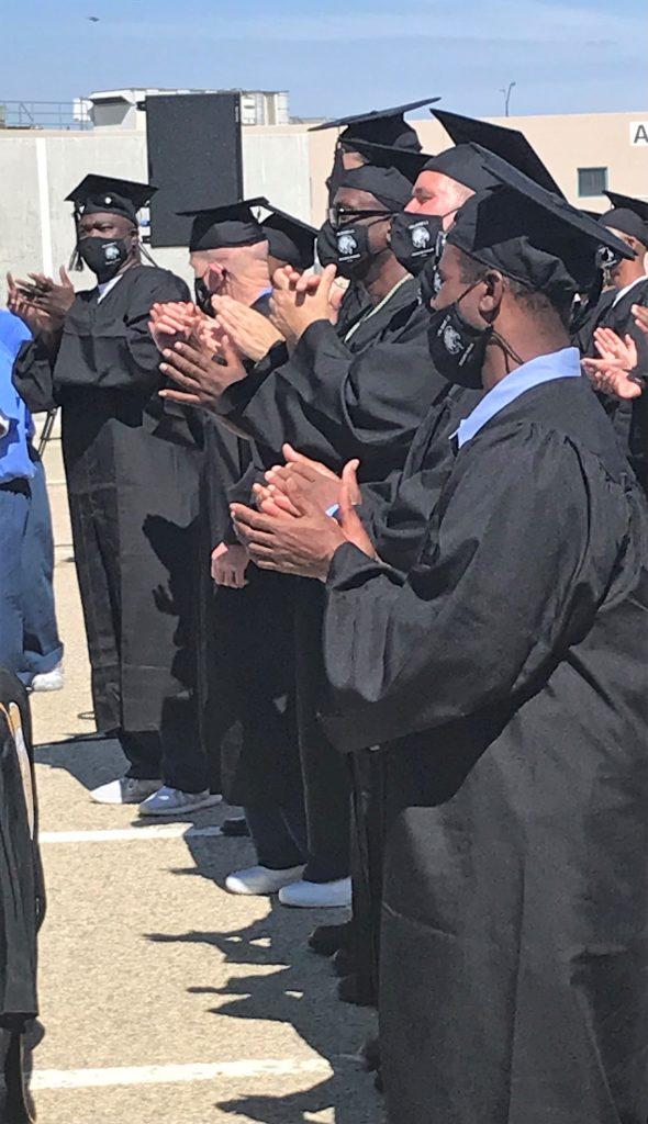 Incarcerated graduates applaud.