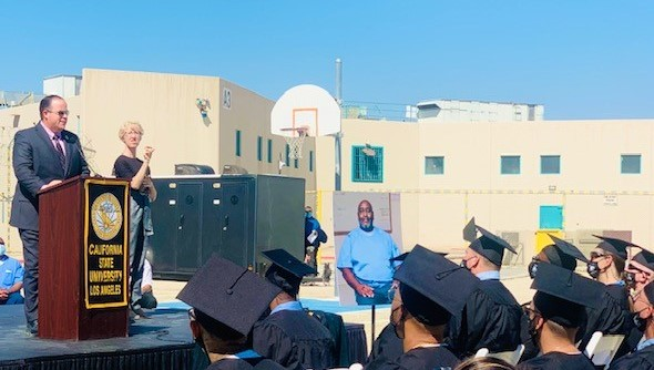 A man at a lectern speaks during a prison graduation.