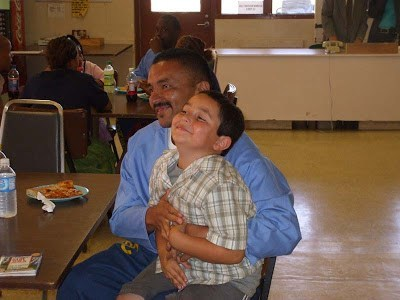 Inmate dad hugging visiting son