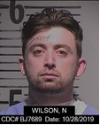 "inmate Noah Wilson is a white male, 5 feet 11 inches tall, weighing 200 pounds with hazel eyes, brown hair, a mustache and goatee, with a tattoo ""Damaged"" above his right eye"