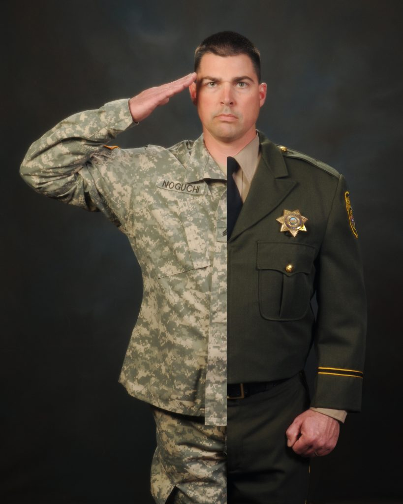 CDCR Officer dressed half in CDCR uniform and half in military uniform, in salute stance.
