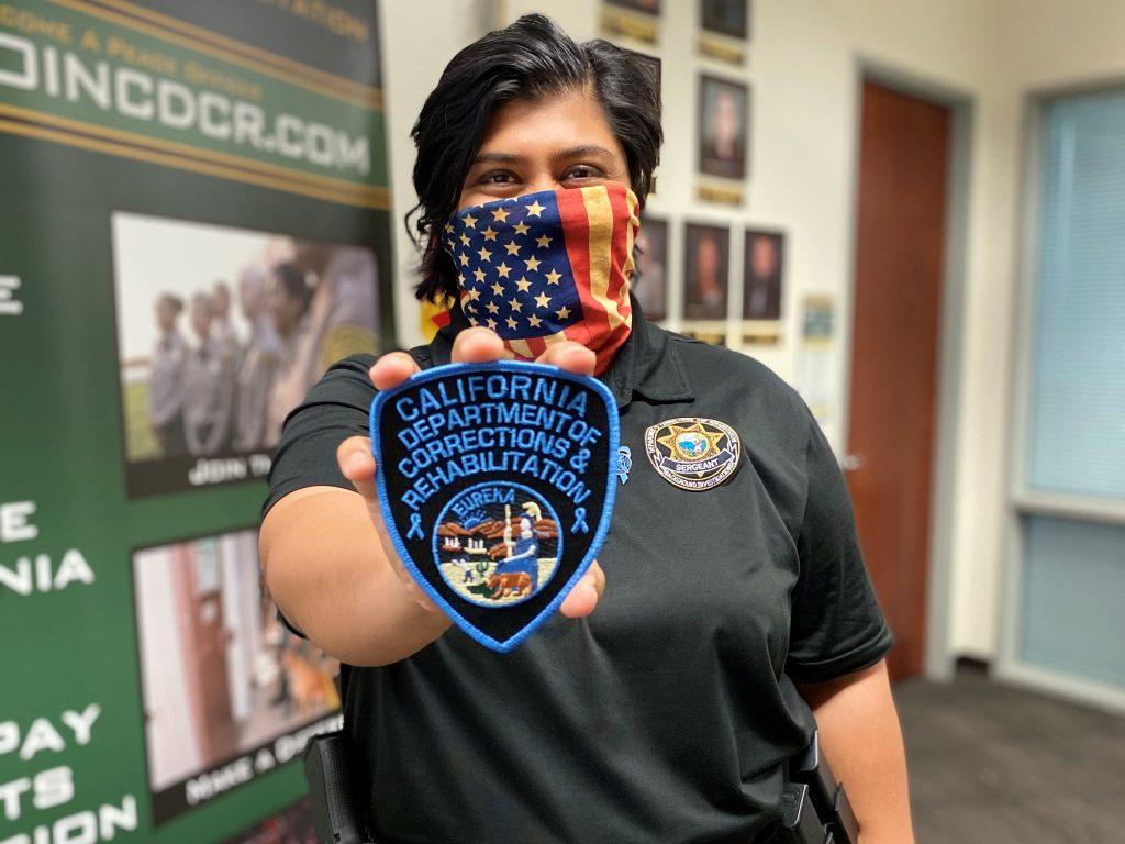CDCR OPOS BIU Sgt. R. Singh holding out a CDCR Blue Patch.