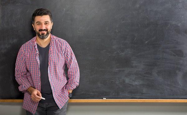teacher standing in front of chalkboard holding chalk