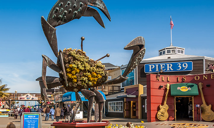 San Francisco Pier 39 tourist area with crab metal and flower display in front of the Hard Rock Cafe