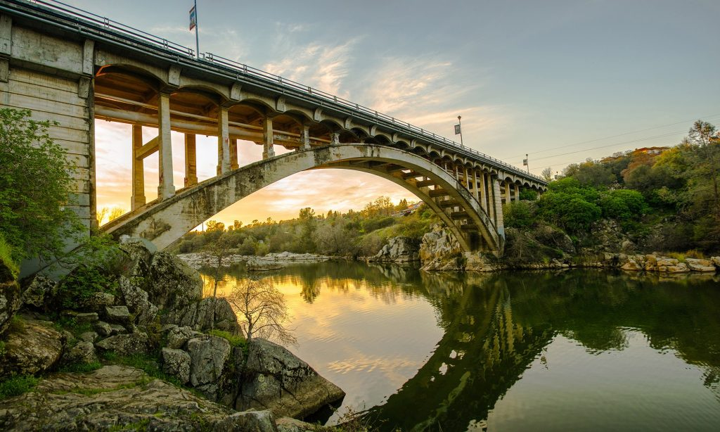 Rainbow Bridge with river underneath during sunset