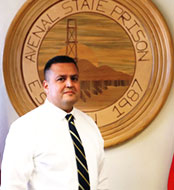 Martin Gamboa standing in front of the Avernal State Prison Seal